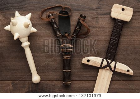 handmade wooden training toy sword, mace and slingshot on the table