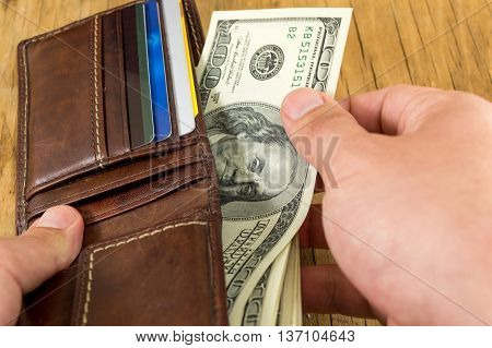 Male Hand Taking Dollar Out Of Wallet