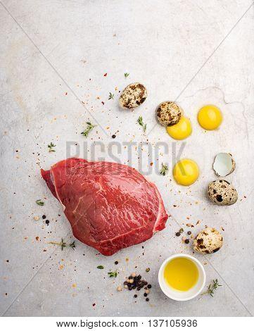 Beaten raw quail eggs and a piece of steak