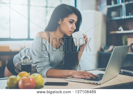 Enjoying coffee at home. Beautiful young mixed race woman drinking her morning coffee and looking at laptop while leaning at the kitchen desk at home