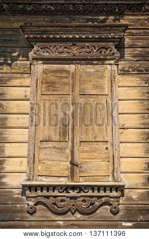 Ancient window with the closed house sun blind in Russia