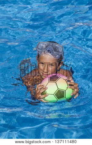 The boy swims in the pool with a ball and a mask of the scuba diver