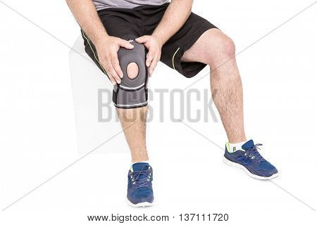 Athlete wearing knee pad on white background