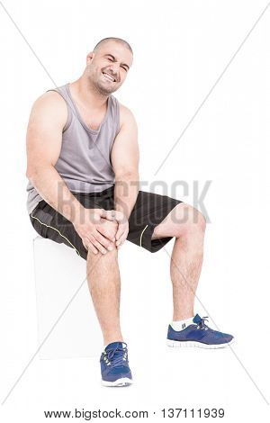 Athlete clutching knee in excruciating pain on white background