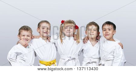Cheerful children in karategi on a gray background