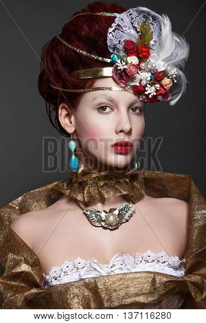 Model in baroque gold attire. Dramatic look.