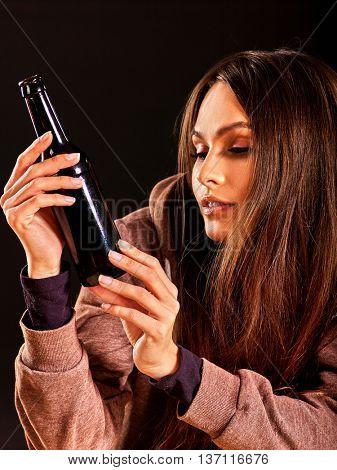 Drunk girl holding bottle of alcohol on dark background. Soccial issue alcoholism.