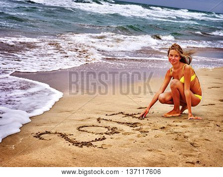 Summer girl sea. Woman in swimsuit written in sand 2017 two thousand and seventeenth year near ocean with waves.