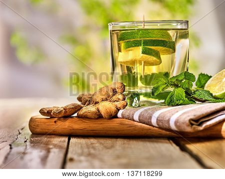 Healthy detox drink with ginger . On wooden boards glass with lime green tea and mint. A healthy mint ginger drink number twenty eight with half slice lime and napkin. Country life. Light background.