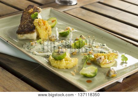 Roast cod with cauliflower, cockles, sprouts & parsley bread sauce