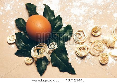 Brown egg on green laurel leaf and excelsior on pack paper background decorated with white flour closeup