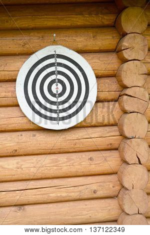 back and white target on wooden log wall