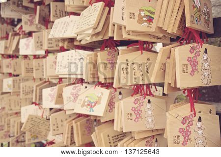 KYOTO, JAPAN - APRIL 29, 2016: Ema plaques at Kiyomizu-dera temple in Kyoto with three monkeys drawing, Japan on April 29, 2016. The Japanese wishes hang inside the temple. Springy textured.
