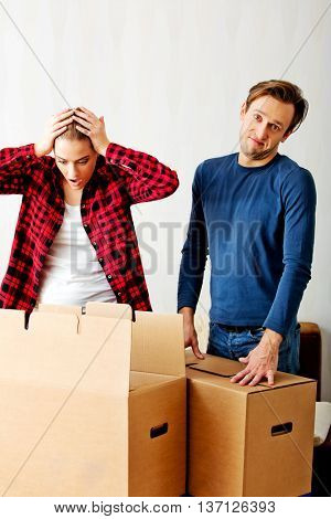 Couple unpaking boxes, woman looking to inside and aghast holding her head
