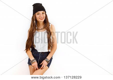 Beautiful woman wearing in black hat and white T-shirt listening music near white wall. Holding a cell phone in hand