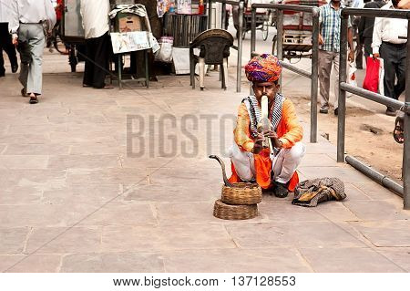 Jaipur India- December 29 2011: A snake charmer is playing the flute for the cobra sitting on the street near Fort Amber
