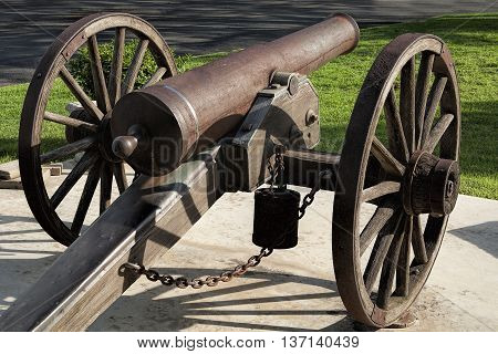 Rusty old civil war canon displayed on a court house lawn in Texas