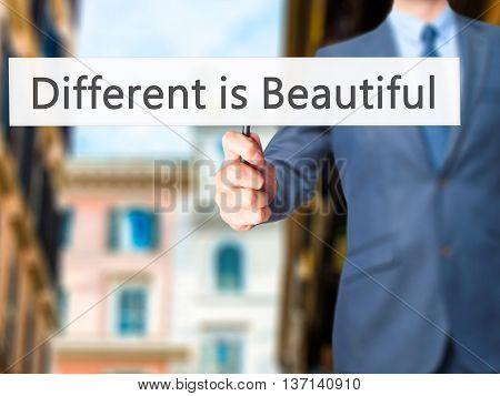 Different Is Beautiful - Businessman Hand Holding Sign