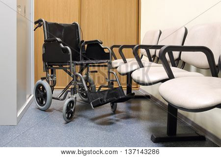 black wheel chair stands in lobby of hospital ready to transport patient
