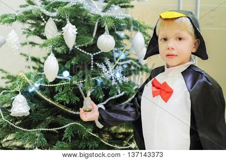 Half-length portrait of boy dressed as penguin standing near Christmas tree in living room, close-up