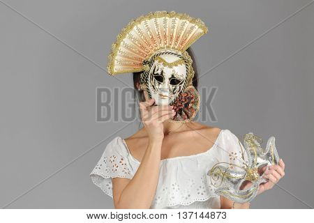 half-length portrait of young woman in carnival mask, holding another mask in hand