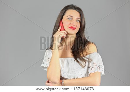 Half-length portrait of woman in white dress talking on phone, looking throw, on gray background