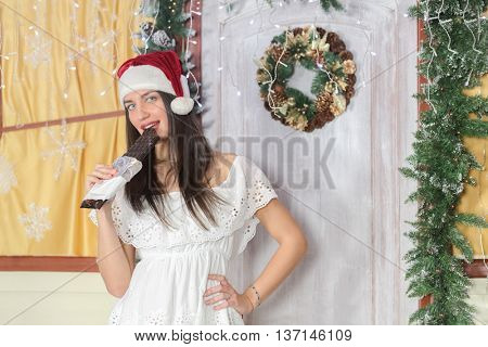 lovely woman with elegant style in Santa cap standing near door of house sham and holding large bar of chocolate, biting into piece