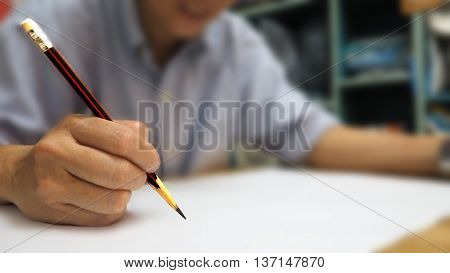 Human take a pencil ready to write on white paper pencil is clearing around are abstract blur