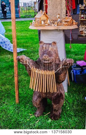 VELIKY NOVGOROD RUSSIA - JUNE 11 2016. Souvenirs at the Russian fair - wooden sculpture of a bear playing a ratchet. Ratchet is a folk noise music instrument.