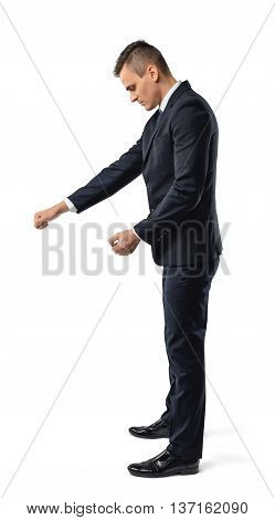 Side view of businessman holding something, isolated on white background. Successful lifestyle. Business staff. Office clothes. Dress code. Presentable appearance.