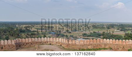 Chettinad India - October 16 2013: Panoramic view on the surrounding region of Thirumayam Fort. Ramparts and battlements in foreground. Battlements look like robot faces.