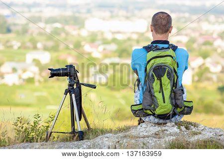 Hiker photographer sitting on a rock looking forward near a camera on a tripod