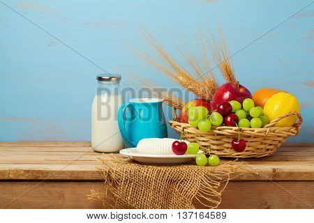 Fruit basket and dairy products on wooden table. Jewish holiday Shavuot background