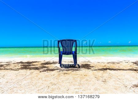 A chair sitting in the sand and looking at the ocean at a Yucatan Peninsula Beach
