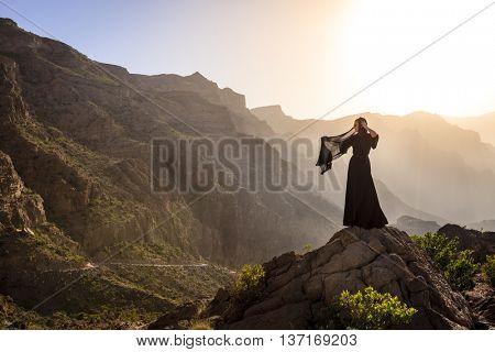 Lone woman in abaya in Al Hajar Mountains of Oman at sunset
