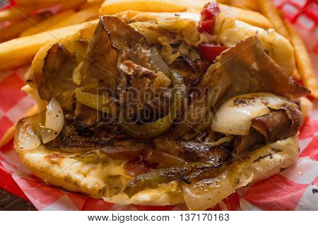 A messy Philly Cheesesteak with onions peppers and mushrooms fries on the side