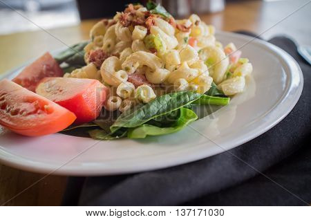 Macaroni salad on bed of spinach greens with tomato wedges and bacon bits