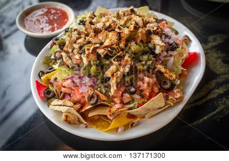 Colorful Mexican nachos with chicken black olives melted cheese jalapenos and more