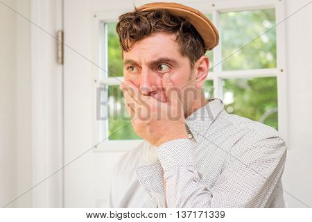Young handsome curly haired man wearing newsboy hat covering mouth