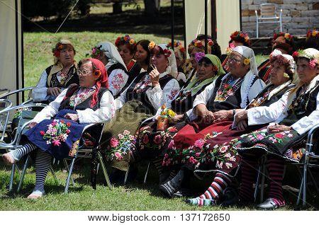 ARBANASI VILLAGE BULGARIA - JUNE 5 2016: Aged Bulgarian women wearing traditional clothing watch performance at the National Folk Festival