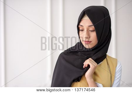 studio portrait of a beautiful young woman of Middle Eastern appearance in the modern Muslim women's clothes and a scarf on her head, on light background classical