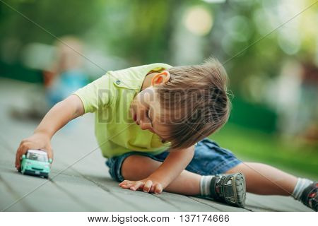 photo of little boy playing with toy car