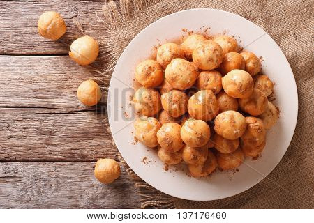 poster of loukoumades donuts with honey and cinnamon close-up on a plate. Horizontal view from above