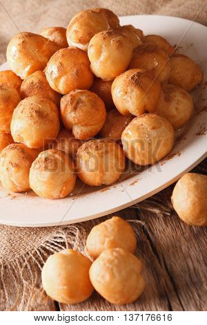 poster of Greek loukoumades donuts with honey and cinnamon close-up on a plate. vertical