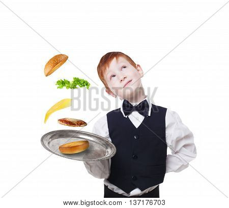 Little waiter dreaming with tray, serving hamburger. Cheeseburger levitates with separated toppings. Flying burger layers. Smiling redhead child boy in suit isolated at white background