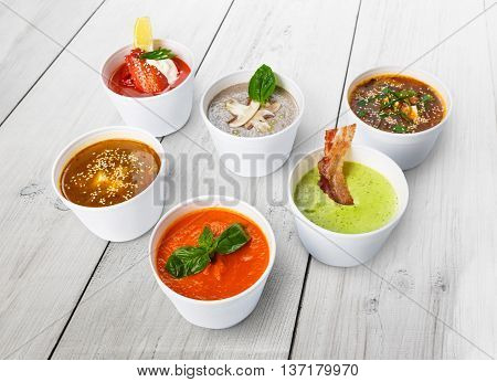 Variety of restaurant hot dishes, healthy food. Japanese miso soup, asian fish soup, russian borscht, english pea soup with bacon, mushroom soup, spanish gazpacho at wood