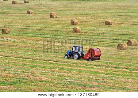 Tractor pulls Round Baler in the background of a field with haystacks