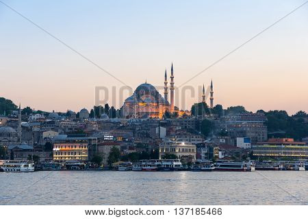ISTANBUL TURKEY - JUNE 20 2015: Night view on the Suleymaniye Mosque and fishing boats in Eminonu Istanbul Turkey