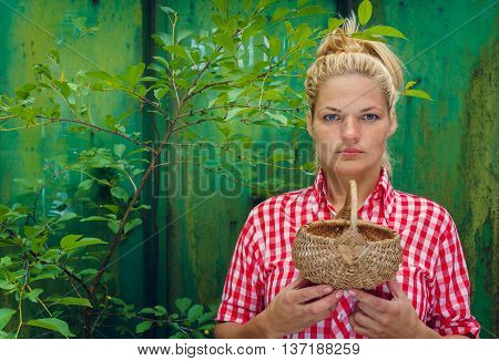 Blonde girl on a green background holding a basket. Rockabilly style. Space for text
