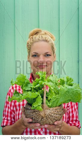 Blonde girl on a turquoise background holding basket with lettuce. Rockabilly style. Space for text